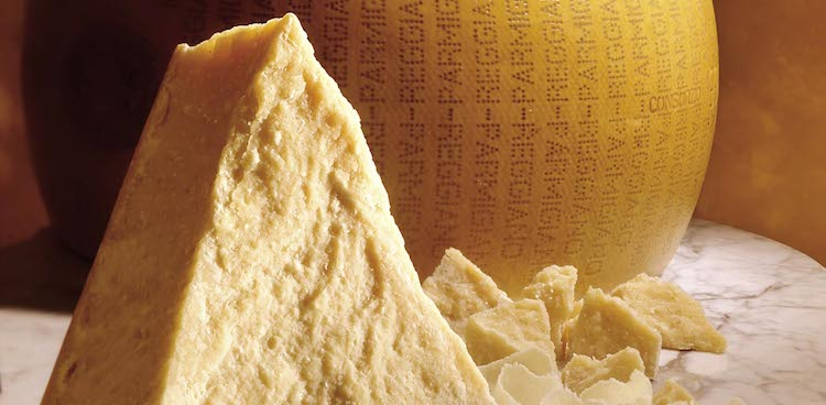 wedge and crumbles of parmigiano cheese in front of wheel