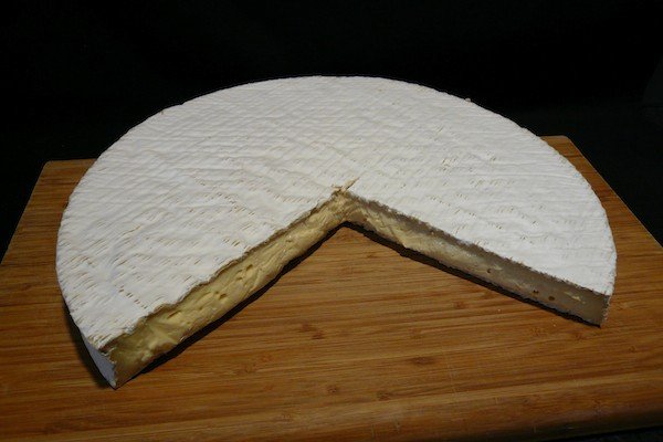 Brie de Meaux cheese with wedge removed