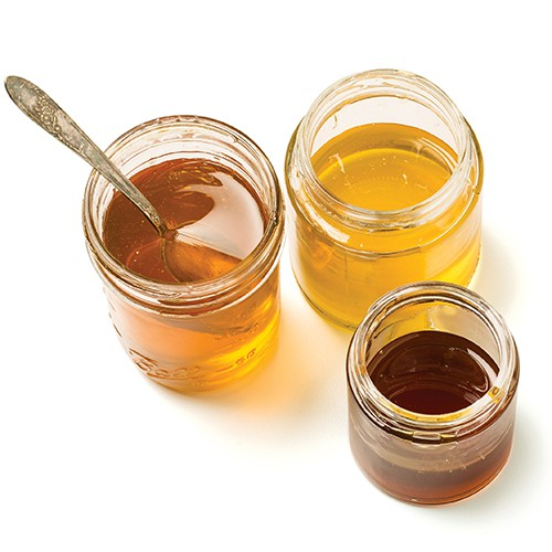 three jars of honey in different hues